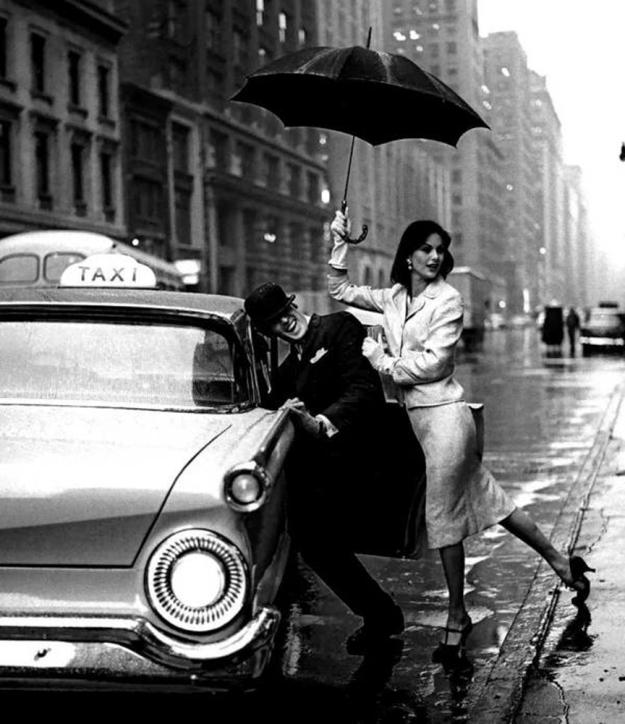 couple-hailing-taxi-rain-umbrellas-vintage-cab.jpg